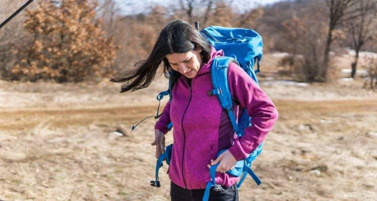 woman putting on a backpack